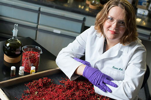 Emory ethnobotanist Cassandra Quave, shown with berries from the Brazilian peppertree.